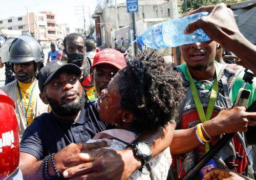 Journalisten helfen einer Kollegin in Port-au-Prince, Haiti, nachdem die Polizei Tränengas gegen eine protestierende Menge einsetzte. reuters