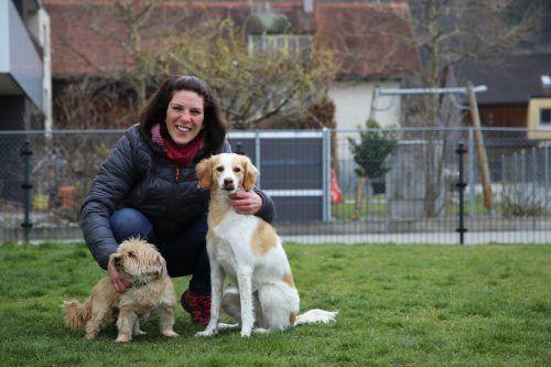 """Bettina Längle mit ihren beiden eigenen Hunden (l.) und mit einigen der vierbeinigen Besucher, die sich in der """"Hundevilla"""" eingefunden haben."""