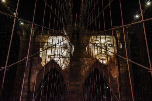 Ein Jahr nach Beginn der Pandemie sind Bilder der mehr als 30.000 Coronaopfer New Yorks auf die Brooklyn Bridge projiziert worden. AFP