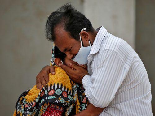 Angehörige eines Mannes, der mit dem Coronavirus gestorben ist, trauern vor einem Spital in Ahmedabad. reuters