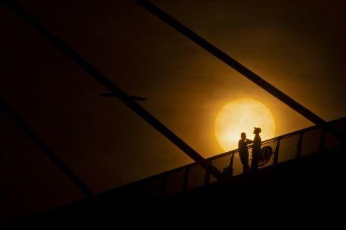 Auf der Muhammad-Baqir-al-Sadr-Brücke im irakischen Basra beobachten Männer den Sonnenaufgang über dem Fluss Schatt al-Arab. AfP