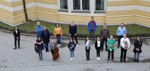 Die acht erfolgreichen Feldkircher Musikschüler präsentieren – mit ihren Lehrpersonen im Rücken – stolz ihre Instrumente.
