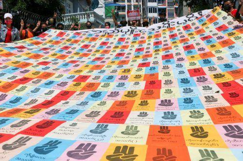 In Yangon, Myanmar, protestieren Demonstranten mit einem Banner, das die Namen vom Militär getöteter Aktivisten zeigt. AP