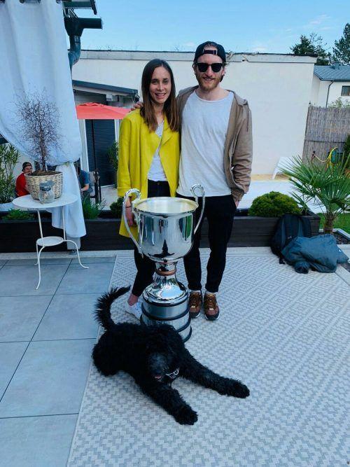 KAC-Stürmer Johannes Bischofberger freut sich mit Freundin Lisa über den Pokal, Hausherr Balu gibt sich von der gelassenen Seite. JOB