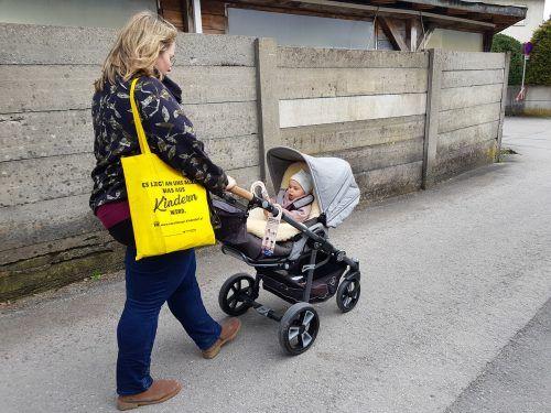 Lisa Harasser ist mit Töchterchen Leoni unterwegs und hat sich für die Verteilung der Türanhänger ein paar Straßen in Lustenau vorgenommen. voki