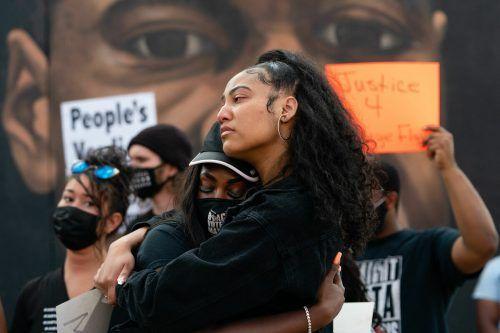 Nach dem Schuldspruch nehmen sich zwei Frauen in Atlanta vor einem Wandbildnis, das George Floyd zeigt, in die Arme. AFP