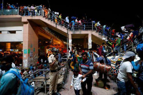 Nachdem ein Lockdown in Neu-Delhi, Indien, verhängt wurde, warten Wanderarbeiter auf Busse, die sie in ihre Heimatdörfer bringen. reuters
