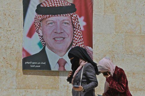 Zwei Frauen passieren in der Hauptstadt Amann ein Poster von König Abdullah II. AFP