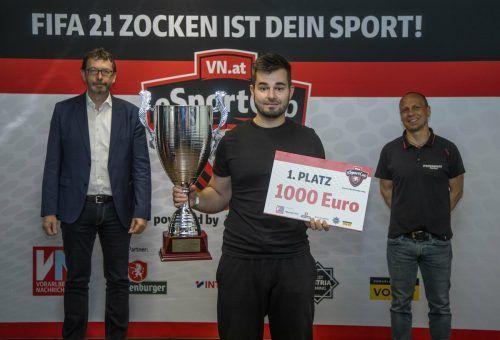 Asko Muratovic präsentiert stolz den Siegerpokal und den Siegerscheck. Im Hintergrund die Sponsorenvertreter Andreas Neuhauser (l.) und Daniel Metzler.