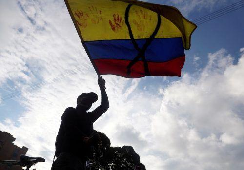 Bei einem Protest gegen Armut und Polizeigewalt in Bogotá schwenkt ein Demonstrant eine kolumbianische Fahne. reuters