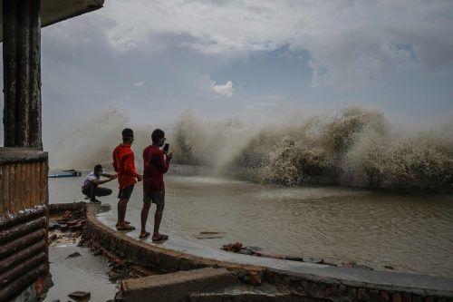 Bewohner der indischen Ostküste in der Bucht von Digha fotografieren Sturmfluten, die der Zyklon Yaas an die Küste peitschen lässt. AFP