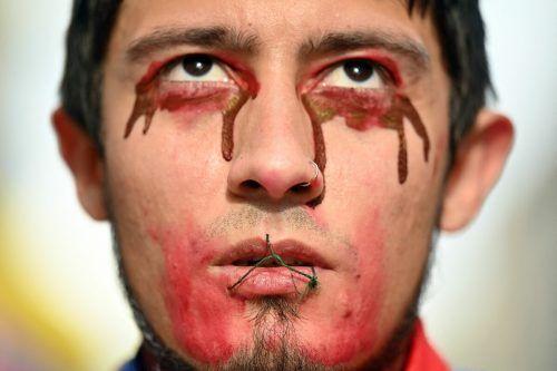 """Ein junger Mann mit einem offenbar zugenähten Mund nimmt in Madrid an einem Protestmarsch mit dem Slogan """"SOS Kolumbien"""" teil. AFP"""