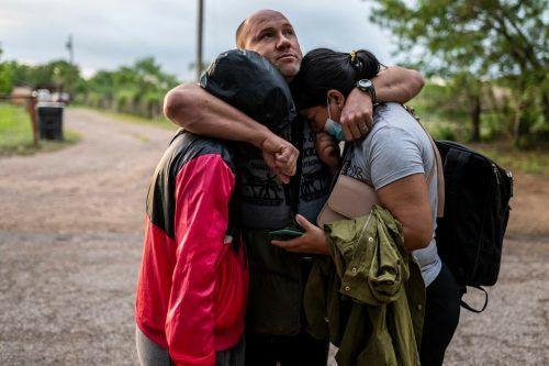 Eine asylsuchende Familie umarmt sich im US-Staat Texas, nachdem die drei von Mexiko aus den Rio Grande überquert haben. AFP
