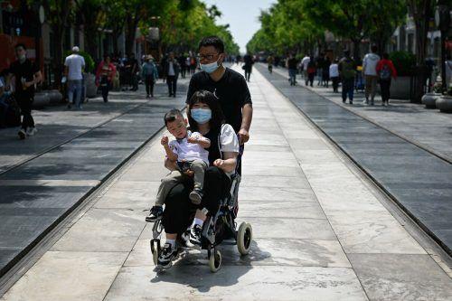 Eine Familie ist in der Hauptstadt Peking unterwegs. AFP