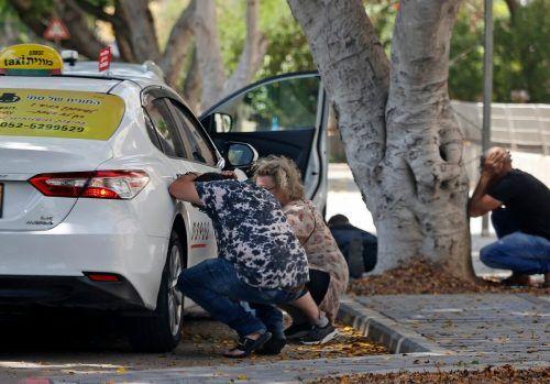 In Aschkelon suchen Menschen hinter einem Auto Deckung.