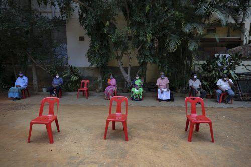 In einer zum Corona-Impfzentrum umfunktionierten Schule im indischen Bangalore warten Menschen auf ihre Immunisierung. AP