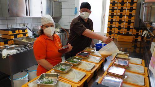 Köchin Anne Jahne und Küchenhilfe Maria bei der Abfüllung der Boxen für das Essen auf Rädern.Egle