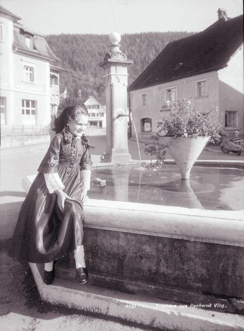 Trachtenaufnahme aus Rankweil. Brunnen haben auch heute noch eine große Anziehungskraft und sind beliebte Treffpunkte und Fotomotive.Sammlung Risch-Lau, Rudolf Zündel (VN), Sammlung Norbert Bertolini, Vorarlberger Landesbibliothek