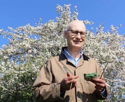 Vor einer Hochstamm-Blütenpracht zeigt der Fachmann Veredelungsmesser, Bast, Baumwachs und Veredelungsreiser.stp/3