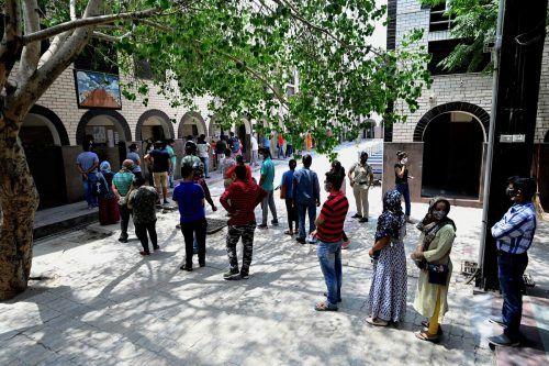 Vor einer Schule in Neu-Delhi warten mehrere Menschen auf ihre Corona-Impfung. Die Situation in Indien bleibt dramatisch. AFP