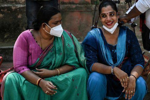 Zwei Frauen warten in einem Gesundheitszentrum im südindischen Chennai auf ihre Corona-Impfung. AFP
