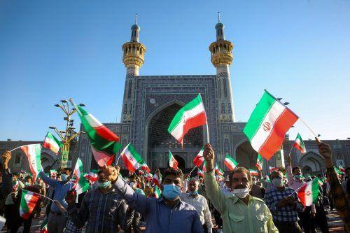 Anhänger des neuen iranischen Präsidenten Ebrahim Raisi jubeln dem Ultrakonservativen beim Imam-Reza-Schrein in Maschdad zu. AFP