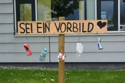Die Sprüche auf den Schildern sollen die Betrachter zum Nachdenken anregen. Der drangehängte Abfall verdeutlicht die Botschaft.