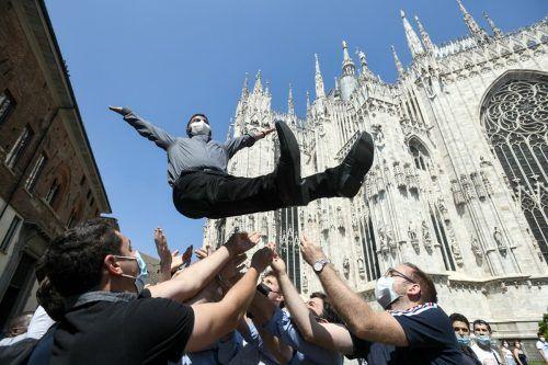Ein katholischer Priester wird nach der Weihezeremonie von Freunden und Familie vor dem Dom im italienischen Mailand groß gefeiert. AFP