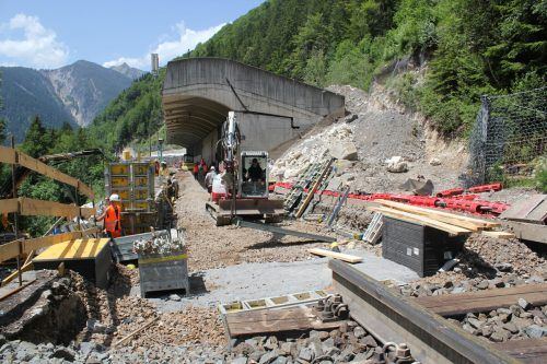 Im Bereich der Löcherwaldgalerie wird derzeit am Untergrund gearbeitet (oben). Neue Oberleitungsmasten wurden per Hubschrauber in Stellung gebracht (unten). VN/JS