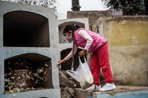 In Lima, Peru, streut ein Mädchen Blütenblätter auf den Sarg einer verwandten Person, die mit dem Coronavirus verstorben ist. AFP