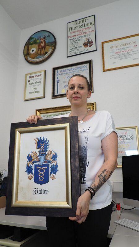 Karin Natter an ihrem Arbeitstisch, an dem neben Urkunden, Auszeichnungen oder Siegeln ...Egle