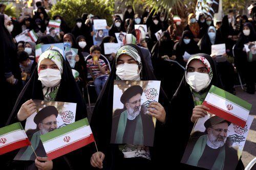 Unterstützer des Hardliners Ebrahim Raisi, des klaren Favoriten bei der Präsidentschaftswahl, schwenken Fahnen und Plakate in der Hauptstadt Teheran. AP