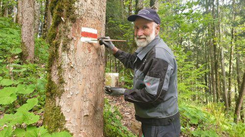 Walter Zudrell markiert eine Tanne weiß-rot-weiß. EST