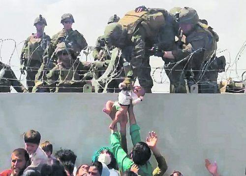 Chaos am Kabuler Airport: Dieses Bild zeigt, wie verzweifelte Afghanen einem US-Soldaten ein Baby über die Absperrung reichen. reuters