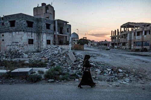 """Eine Syrerin läuft durch das kriegszerstörte al-Rakka, einst inoffizielle """"Hauptstadt"""" des IS. Die Terrormiliz wurde 2017 vertrieben. AFP"""