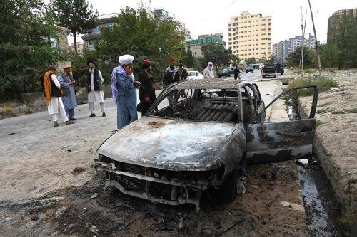 Taliban untersuchen ein zerstörtes Auto nahe dem Airport in der afghanischen Hauptstadt. AFP