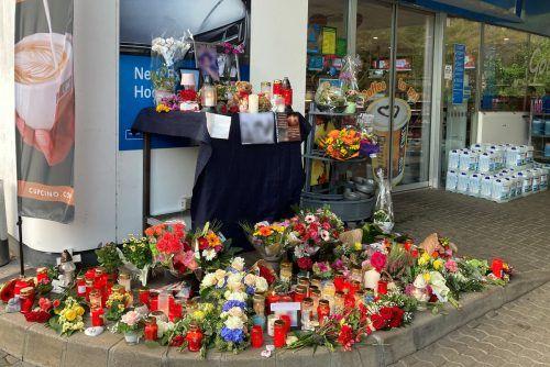 Anrainer und Kunden haben Blumen und Kerzen vor der Tankstelle aufgestellt. dpa