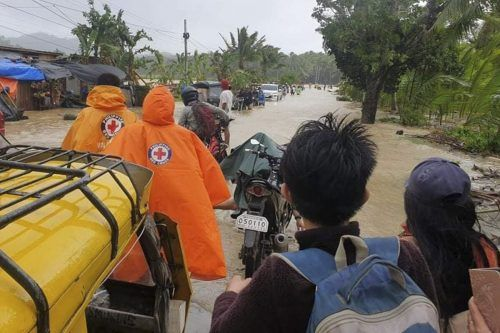Rot-Kreuz-Mitarbeiter helfen Menschen aus überschwemmten Gebieten. ap