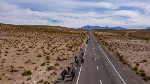Venezolanische Migranten gehen die Straße zwischen der Grenzstadt Colchane und Iquique, Chile, entlang. AFP